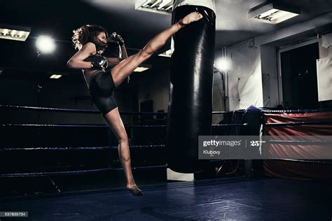 Female Kickboxer Training With A Punching Bag High-Res